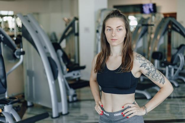 魅力的なスポーツ少女は、ジムのシミュレーターの背景に立っています。健康的な生活様式。