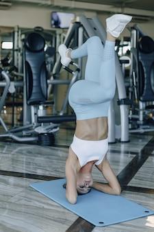魅力的なスポーツ少女は、ジムで彼女の頭の上に立っています。健康的な生活様式。
