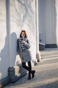 晴れた日に歩くコートで眼鏡をかけている魅力的な若い女の子