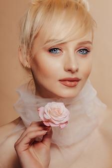 Довольно привлекательная девушка со светлыми волосами, модная съемка, роза, простой фон