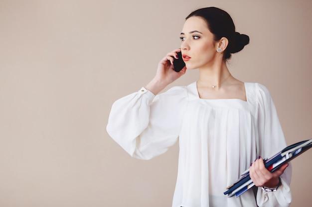 Деловая женщина разговаривает по телефону с документами в руках