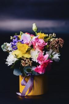 暗い背景上のバスケットの色の花束