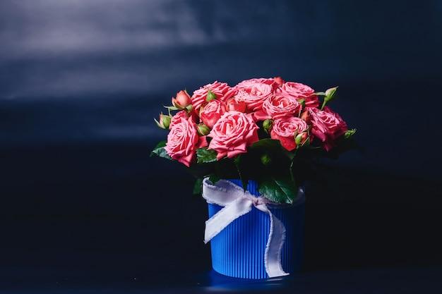 Розовый куст в корзине сорта барбадос на темном фоне