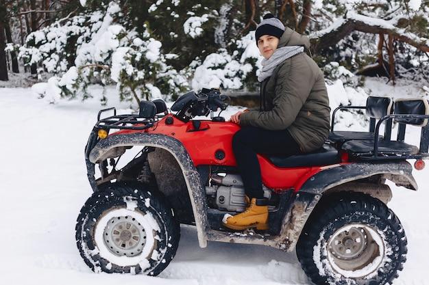 男は雪の天気の中でバイクに乗る