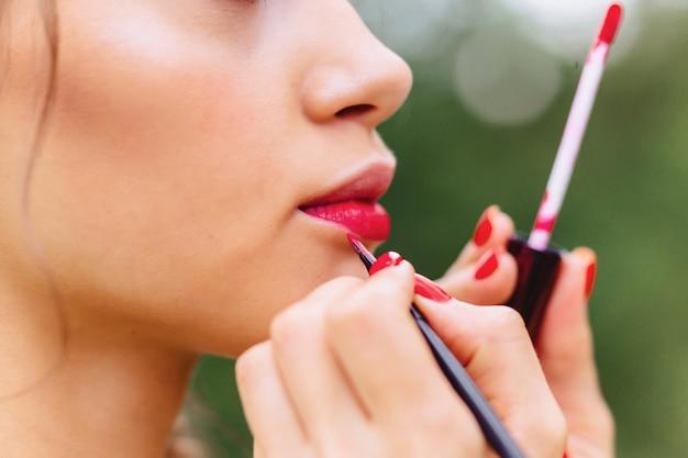 女の子が路上で赤で唇を塗料します。