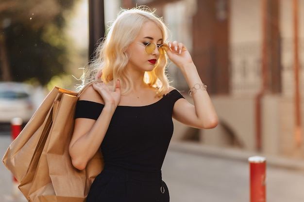 Белокурая привлекательная девушка в солнечных очках после покупок в лучах летнего солнца