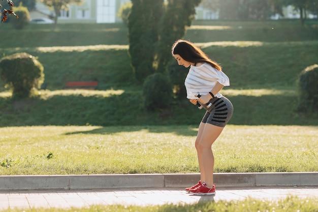 Фитнес девушка делает упражнения с гантелями на закате на траве снаружи