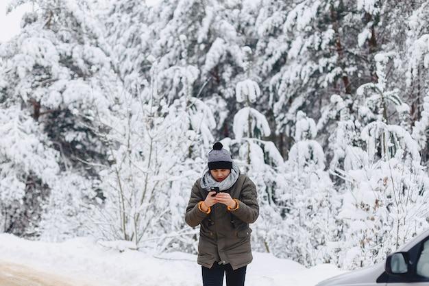 Парень, идущий по заснеженной дороге возле соснового леса с телефоном