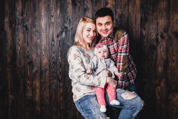 Мать и отец с ребенком в барном кресле на фоне деревянной стены