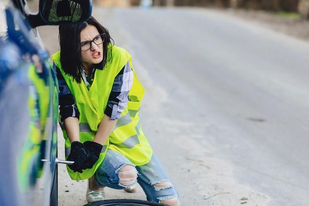 魅力的な女の子は一人で道路から車からホイールを削除します