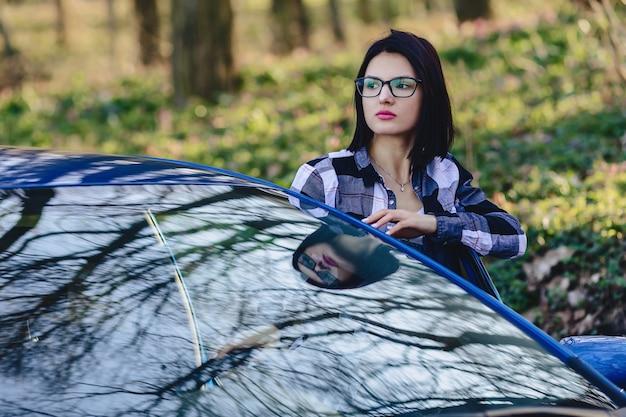 魅力的な運転手の女の子が車の開いているドアの外に見える