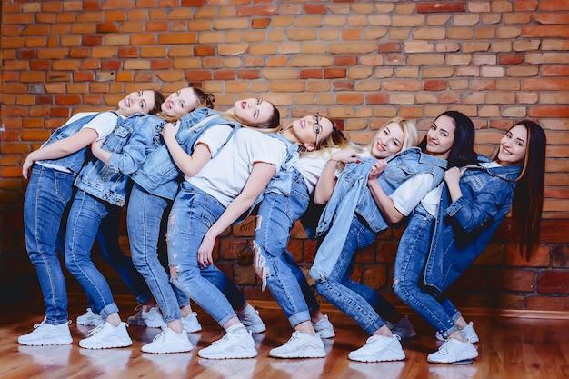 レンガの壁の背景でジーンズの女の子
