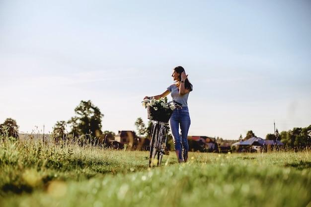 女の子は日当たりの良い光の後ろに自転車でフィールドに子犬と歩く