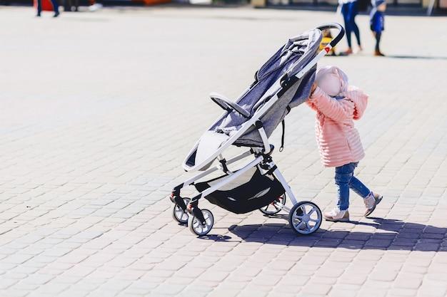 赤ちゃんが路上で馬車で歩く