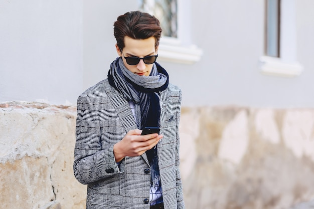 路上で携帯電話とサングラスでスタイリッシュな若い男