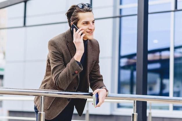 Стильный привлекательный парень в куртке с телефонным паспортом и билетами