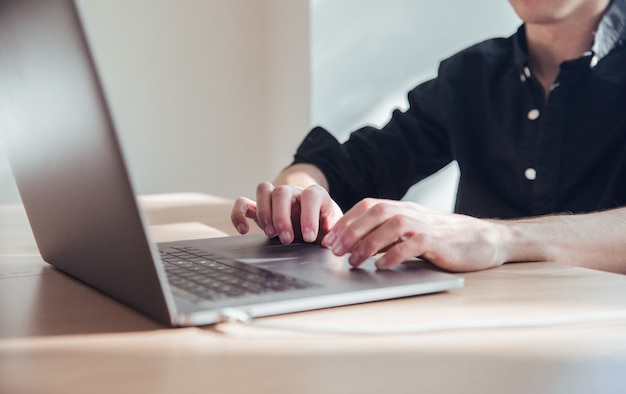 男の手がオフィスで黒いノートパソコンでの作業