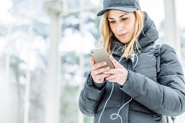 彼女の携帯電話で音楽を聴いている女の子