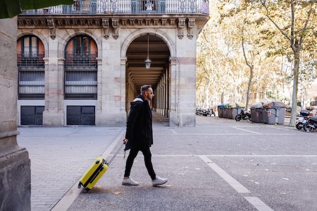 Молодой человек гуляет с чемоданом