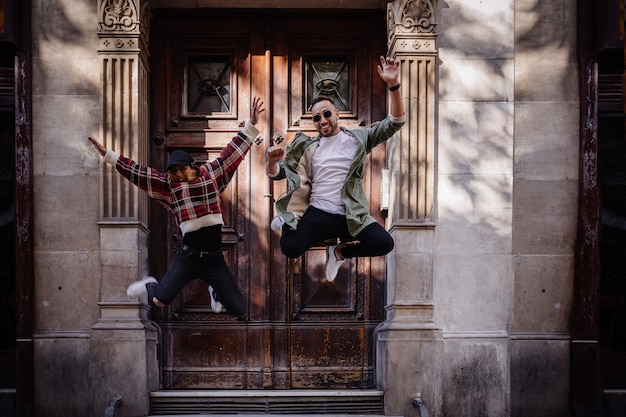 若いカップルが路上でジャンプ