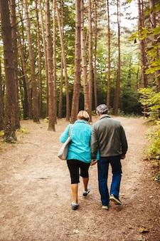 Пожилая пара гуляет по лесу