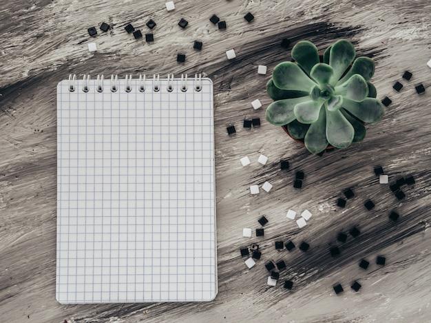 灰色のテーブルの上に花とノート。平らに置きます。