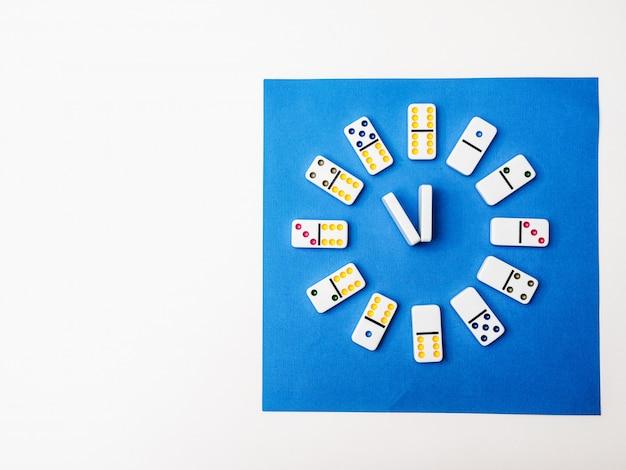 ドミノ時計は白青の背景に。遊ぶ時間
