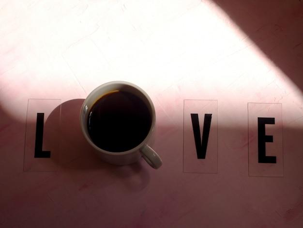Слово любовь с чашкой кофе.