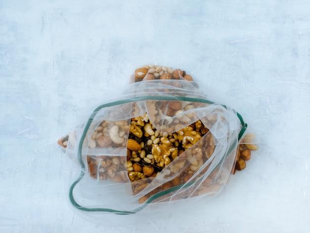 さまざまなナッツが入った再利用可能なメッシュバッグ。廃棄物ゼロのコンセプト。