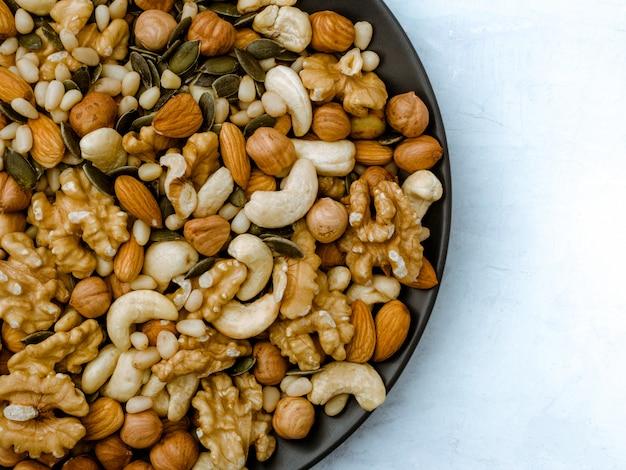 さまざまな種類のナッツ。カシューナッツ、ヘーゼルナッツ、アーモンド、クルミ、杉