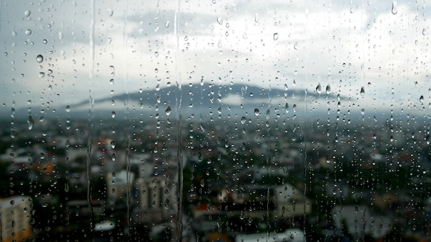 Капли дождя на окне и горы с городом в размытия фона.