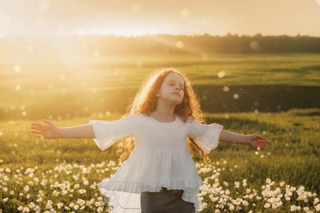 巻き毛の女の子は彼女の目を閉じ、屋外の牧草地に新鮮な空気を吹いて呼吸しています。