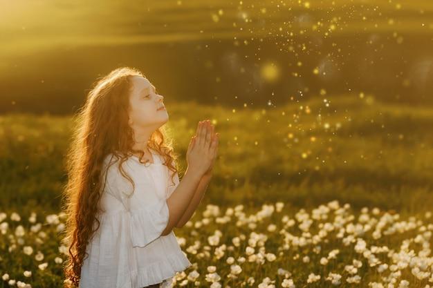 祈りを持つ少女。平和、希望、夢の概念。