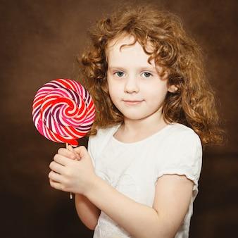 茶色で調色、大きなカラフルなロリポップを保持している小さな女の子。