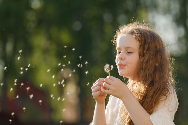 かわいい女の子が屋外にタンポポを吹いています。