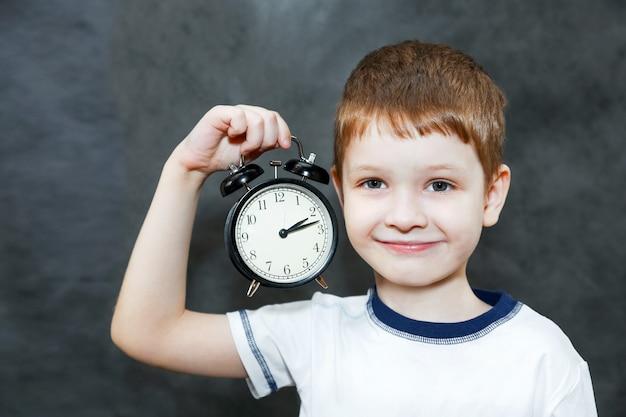 目覚まし時計を保持している小さな男の子。