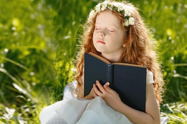 小さな女の子が祈って彼女の手を組んで
