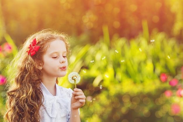 Счастливый ребенок девочка дует одуванчик