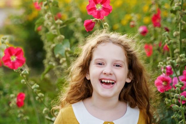 幸せな目を持つ、白い歯を見せている小さな女の子。