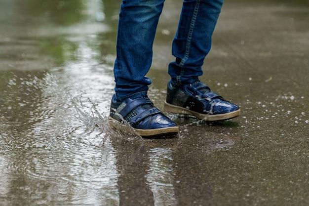 スニーカーのクローズアップで子供の足、子供は水たまりでジャンプします。健康、幸せな子供時代のコンセプトです。