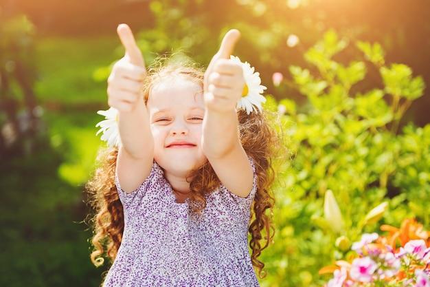 親指を現して、彼女の毛でデイジーと笑っている女の子。