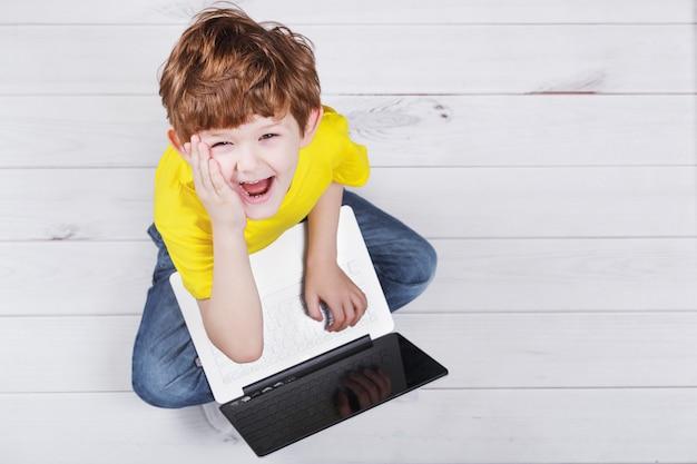 暖かいラミネートまたは寄木細工の床でノートに遊んで驚いた子供。
