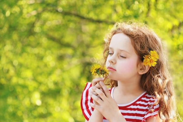 小さな女の子は彼女の目を閉じてフィールドに黄色のタンポポを吸います。