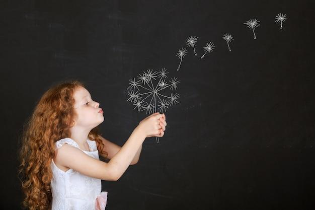 黒板を描くとタンポポを吹く少女。
