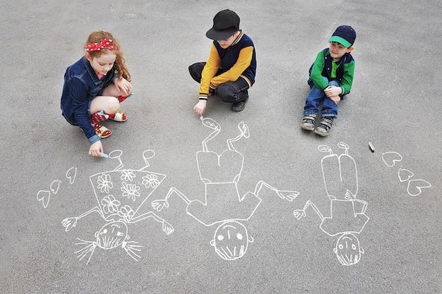 子供たちは春の公園のアスファルトの上で太陽を描いています。