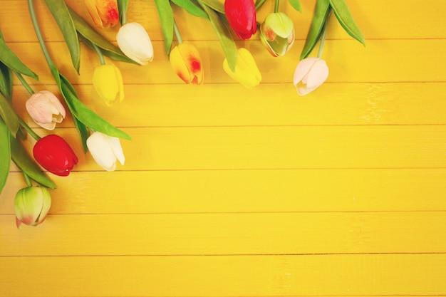 軽い木製の背景にチューリップの花。