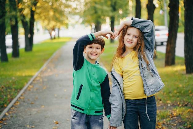 秋の公園で手を繋いでいる子供たち。