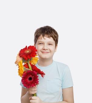 Маленький мальчик с букетом цветов герберы.