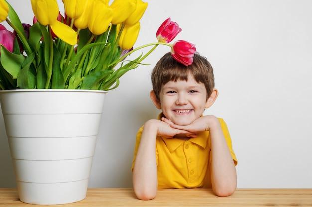 チューリップの花束を持つ赤ちゃんを笑っています。