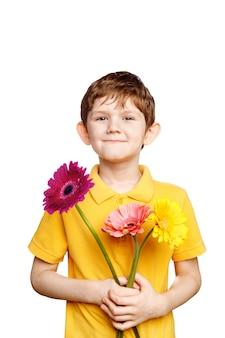 Смеющийся мальчик с букетом цветов герберы.